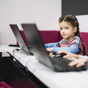 portrait-of-a-little-girl-looking-at-camera-sitting-with-laptop-in-the-classroom