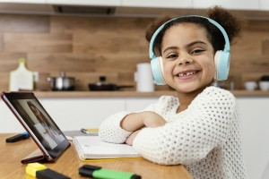 side-view-of-smiley-little-girl-during-online-school-with-tablet-and-headphones